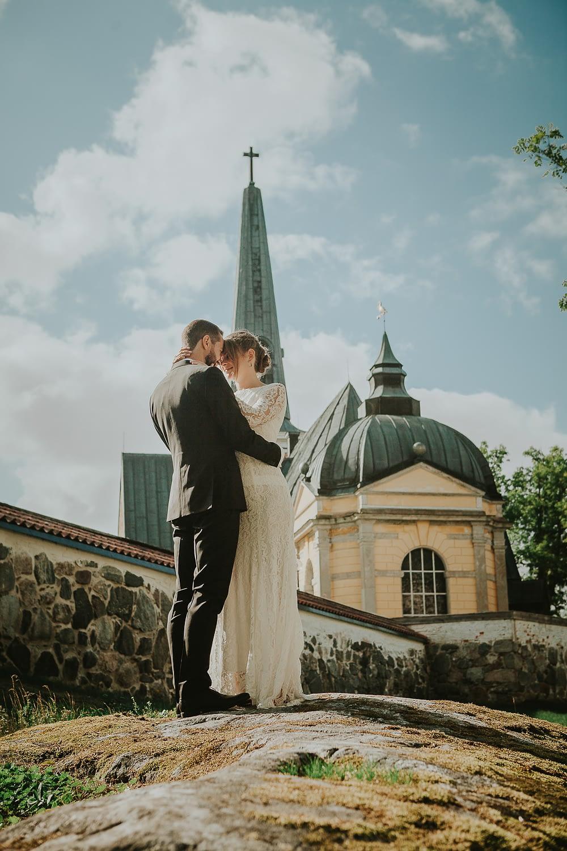 couple câlin devant l'église où ils vont se marier