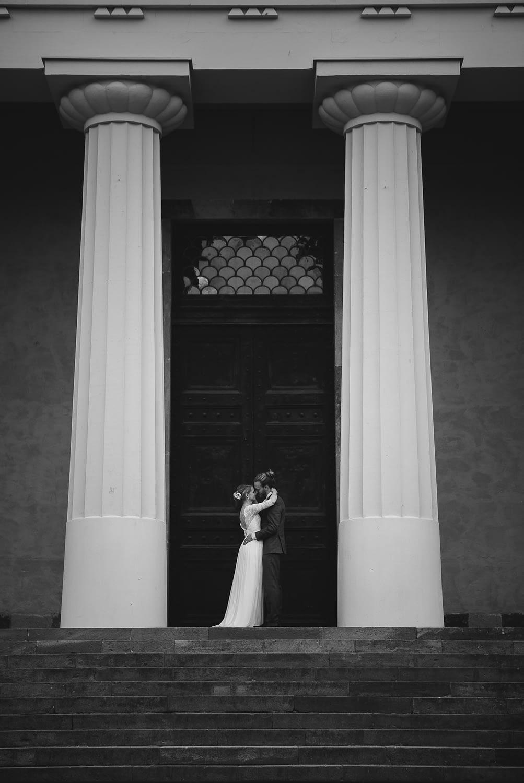 seance photo de couple marié qui embrasse entre deux grandes colonnes