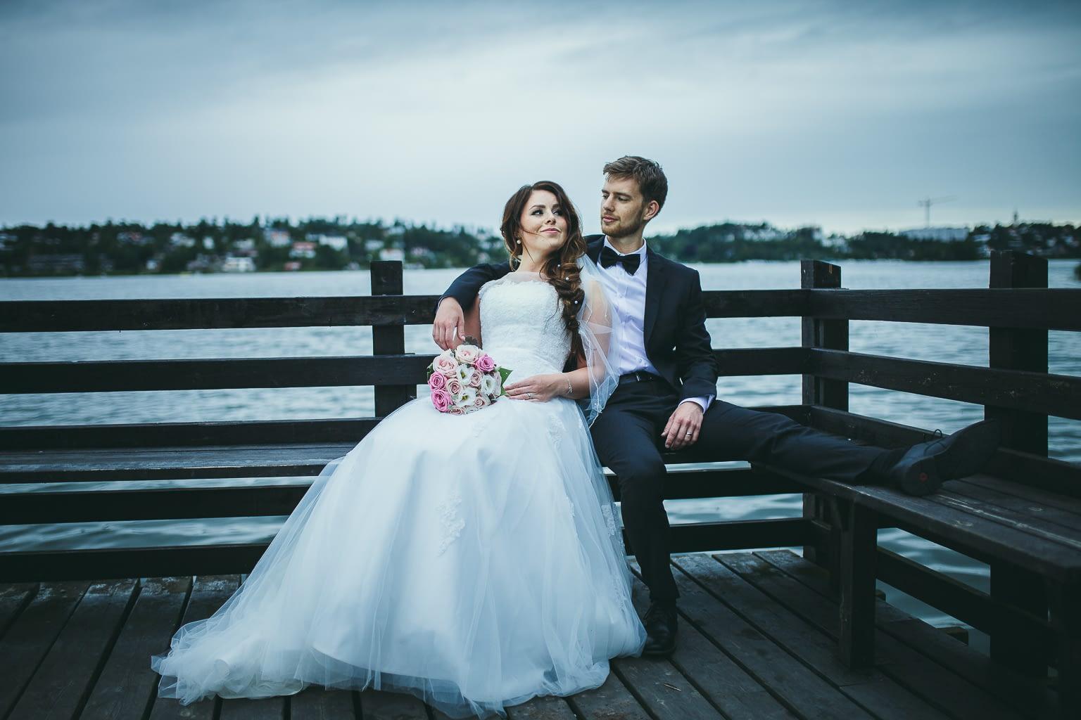 Couple nouvellement marié assis sur un banc posant à leur séance photo de mariage