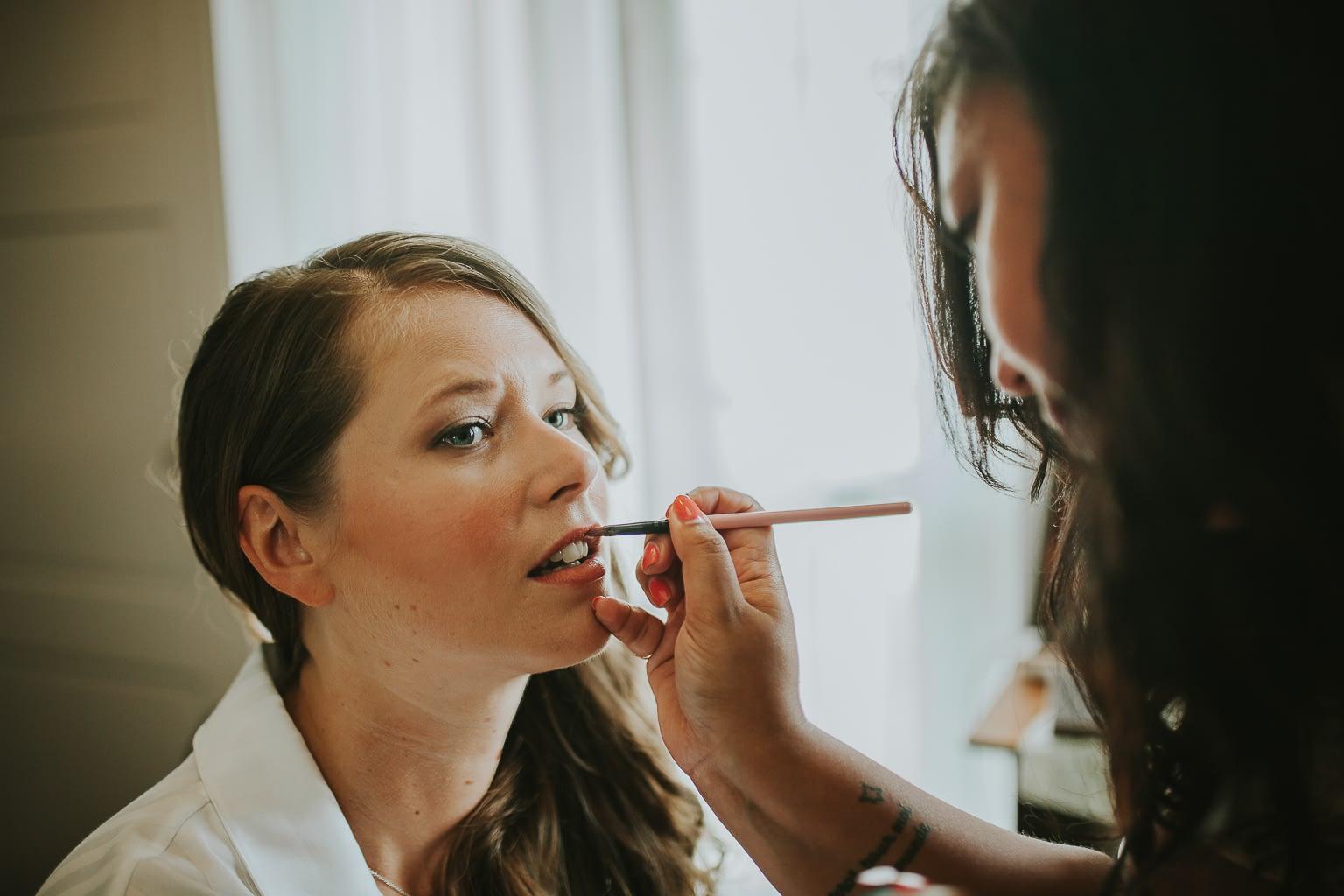 mariée se prépare pour son mariage. la maquilleuse peint ses lèvres