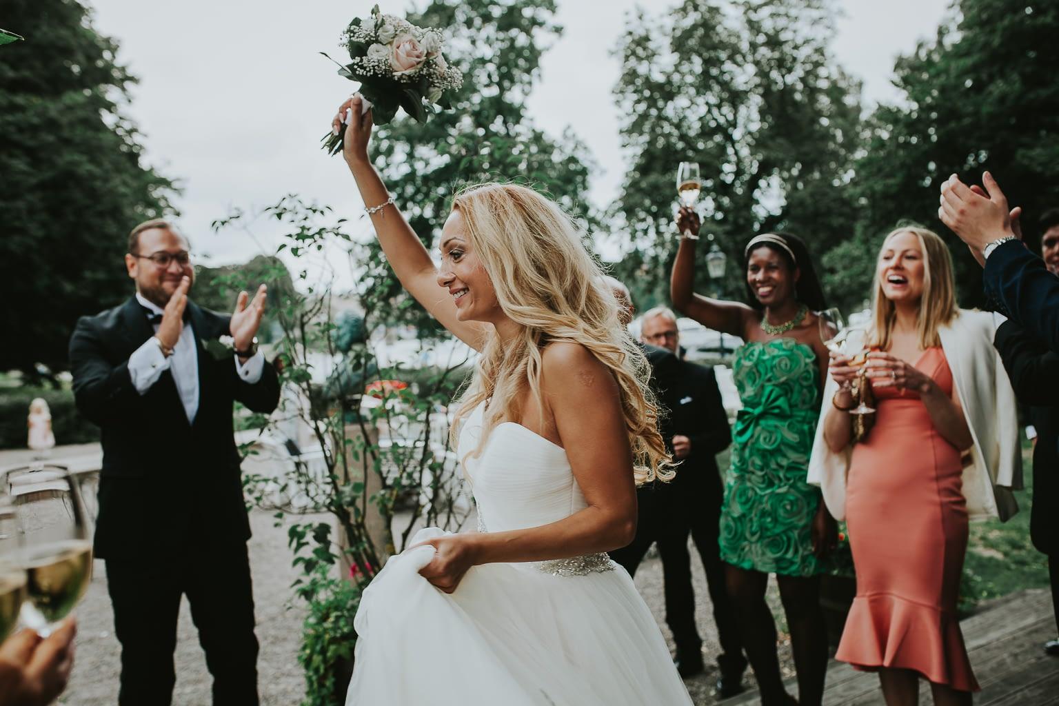 mariée jetant son bouquet de fleurs a son mariage