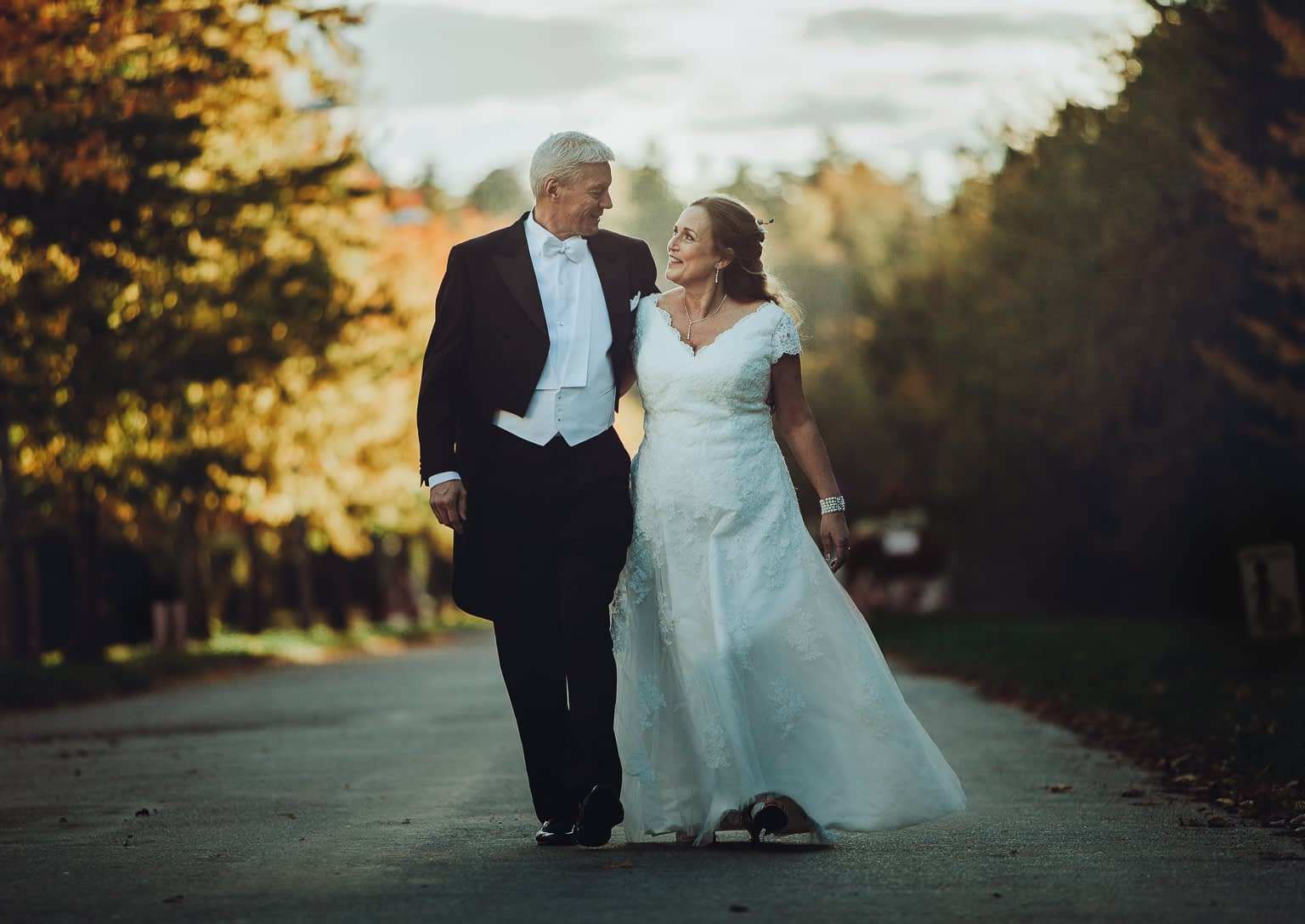 vieux couple marié se baladent en automne avec les arbres oranges autour d`eux